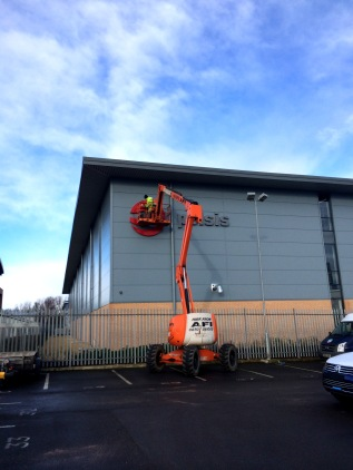 Metal lettering signage being fixed in position using access equipment by Ad Bell